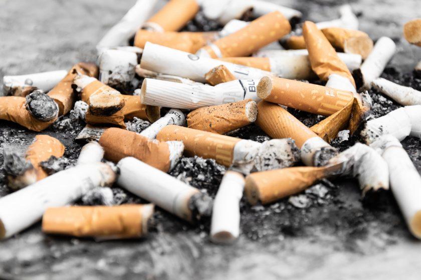 orange cigarette butts on black surface